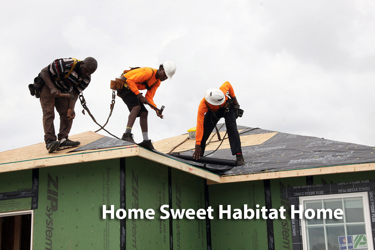 roofers laying atlas roofing underlayment on Habitat for Humanity home